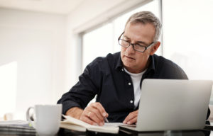 Man doing paperwork in front of a laptop