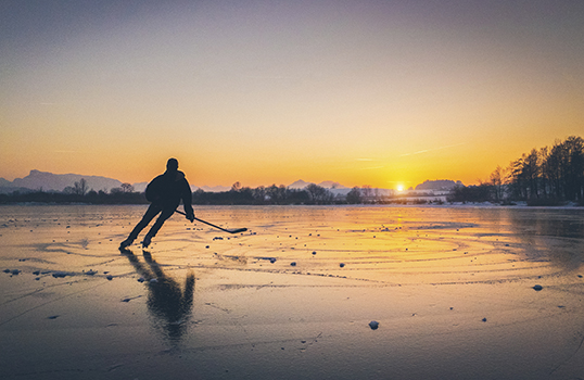 Person playing hockey on a lake in Canada