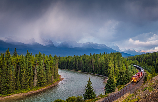 Photo of train tracks along river in Canada