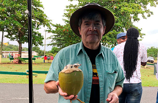Man holding coconut and wearing a hat - locum tenens pediatrician